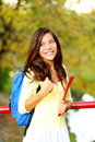 Young woman adult student in autumn back to school park going on university college asian girl smiling happy pretty mixed race Stock Photography