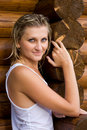 Young woman against the wall of a log timber. Royalty Free Stock Image