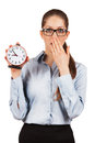 Young woman with an alarm clock in a hand surprised Stock Image