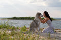 Young woman with alaskan malamute dog adult her favorite pet on the beach in the evening Stock Photo