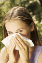 Young woman with allergy during sunny day is wiping her nose Royalty Free Stock Photo