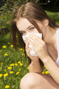 Young woman with allergy during sunny day is wiping her nose Stock Photo
