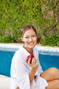Young woman with apple at pool attractive red swimming Royalty Free Stock Images
