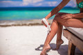 Young woman apply cream on her smooth tanned legs tropical beac Royalty Free Stock Images