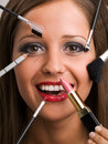 Young woman applying make up close of face with all kinds of tools brush lipstick etc Stock Photos