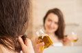 Young woman applying oil mask to hair tips Royalty Free Stock Photo