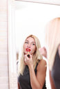Young woman applying red lipstick blonde Stock Photo