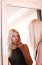 Young woman applying red lipstick blonde Royalty Free Stock Photography