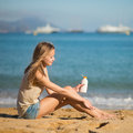 Young woman applying sunscreen on her legs Lizenzfreie Stockfotos