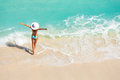 Young woman with arms apart on sand beach white hat in striped swimsuit standing in waves of ocean the of during holidays Royalty Free Stock Photos