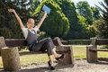 Young woman with arms up sitting at the park Stock Photography