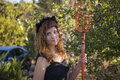 Young woman as cat on Halloween picking apples with fruit picker Royalty Free Stock Photo
