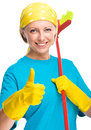 Young woman as a cleaning maid holding broom and showing thumb up gesture isolated over white Royalty Free Stock Image