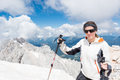 Young woman ascending a mountain girl with trekking poles Stock Photography