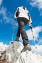 Young woman ascending a mountain ridge with trekking poles Royalty Free Stock Photos