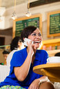 Young woman in an asian coffeeshop enjoying her leisure time a cafe drinking coffee or cappuccino and is on the phone at the Royalty Free Stock Photos