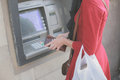Young woman at atm a is withdrawing money from an Royalty Free Stock Image
