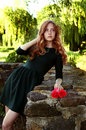 Young woman with auburn hair in the swamps posing red flowers Royalty Free Stock Images