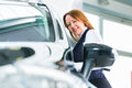 Young woman with auto in car dealership beside a new obviously she is buying the or making a test drive Royalty Free Stock Photography