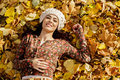 Young woman at autumn forest lying on leaves Royalty Free Stock Photos