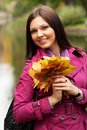 Young woman with autumn leaves in park happy Stock Image