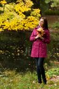Young woman with autumn leaves in park happy Royalty Free Stock Photo