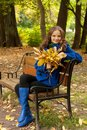 Young woman with autumn leaves sitting on bench elegant Royalty Free Stock Photo