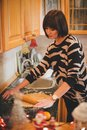 Young woman baking christmas cookies at the decorated kitchen on eve Royalty Free Stock Image