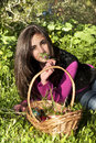 Young woman with basket of eggs picking flowers in a field Stock Photography