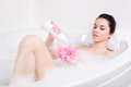 Young woman in a bath with foam sponge in hand beautiful Royalty Free Stock Photo