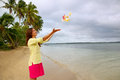 Young woman on a beach throwing flowers in the air ofu island tonga Stock Photography