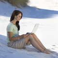A young woman on a beach working on a laptop Royalty Free Stock Photography