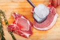 Young woman beating a steak in the kitchen Stock Images