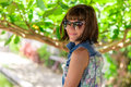 Young woman in beautiful dress and sunglasses posing in gazebo. Tropical island Bali, Indonesia. Portrait of young Royalty Free Stock Photo