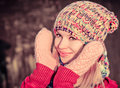 Young woman beautiful happy smiling face winter time wearing knitted hat and scarf with mittens lifestyle concept and christmas Royalty Free Stock Photo