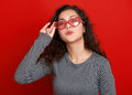 Young woman beautiful portrait flying kiss, posing on red background, long curly hair, sunglasses in heart shape, glamour concept Royalty Free Stock Photo