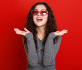 Young woman beautiful portrait, posing on red background, long curly hair, sunglasses in heart shape, glamour concept Royalty Free Stock Photo
