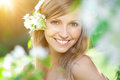 Young woman with a beautiful smile with healthy teeth with flowers. Face of a beautiful positive girl Concept on the subject
