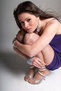 Young woman beauty fashion pose crouched over grey Royalty Free Stock Photography