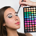 Young woman at beauty salon applying eye shadows eye shadow brush make up Royalty Free Stock Image