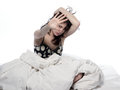 Young woman in bed awakening tired insomnia hangover one a white sheet on white background Royalty Free Stock Images