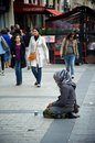 Young woman begging for money on her knees at the champs elysees Royalty Free Stock Photography