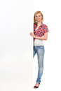 Young woman behind a white banner cheerful blond standing big full length studio shot isolated on Royalty Free Stock Images