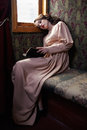 Young woman in beige vintage dress of early th century reading book coupe retro railway train Stock Images