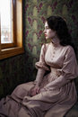 Young woman in beige vintage dress of early th century sitting looking trough the window coupe retro railway train Royalty Free Stock Photography
