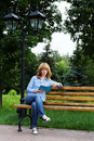 Young woman on a bench reading a book Royalty Free Stock Photo