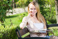 Young woman on bench reading book Royalty Free Stock Photo
