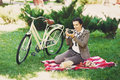 Young woman with bicycle at the picnic in the park Royalty Free Stock Photo