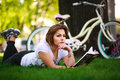 Young woman with bicycle reading book in city park on grass Royalty Free Stock Photo