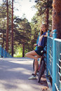 Young woman with bicycle standing on bridge relaxing sexy bike in a country road Royalty Free Stock Photos